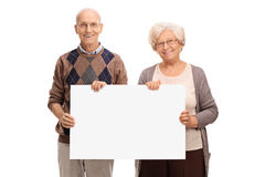 Senior couple posing with a signboard stock images