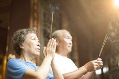 Senior couple praying buddha with incense stick. At temple royalty free stock images