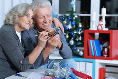 Senior couple preparing for Christmas. Portrait of smiling senior couple preparing for Christmas coloring pine cone decoration Royalty Free Stock Image