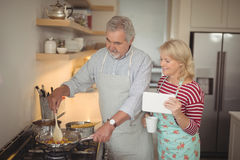 Senior couple preparing food in kitchen. At home Royalty Free Stock Images