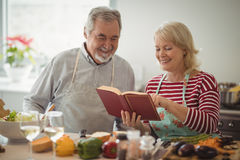 Senior couple preparing food in kitchen. At home Stock Image