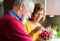 Senior couple preparing food in the kitchen. An old men and women inside the house Stock Photo