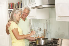 Senior Couple Preparing Meal At Cooker Royalty Free Stock Photography