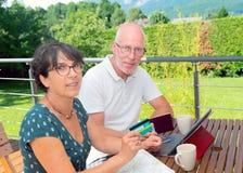 Senior couple preparing vacation trip. A senior couple preparing vacation trip, on her terrace garden Stock Images