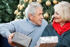 Senior Couple With Presents In Christmas Store Royalty Free Stock Photo