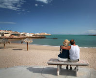 Senior Couple - Puertocitos Baja. A baby boomer husband and wife tourists enjoy a quiet moment and incredible view of the Sea of Cortez while sitting on a bench Stock Image