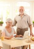 Senior couple purchasing on Internet. Happy senior couple using laptop computer, purchasing on Internet with credit card at home, smiling at camera Royalty Free Stock Photography