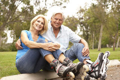 Senior Couple Putting On In Line Skates In Park Stock Image