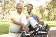 Senior Couple Putting On In Line Skates In Park Royalty Free Stock Image