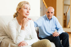Senior couple after quarrel. Couple after quarrel in room at home Stock Photo