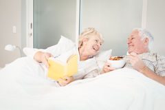 Senior couple reading book in bed Royalty Free Stock Images