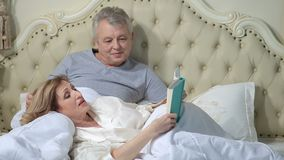 Senior couple reading a book in bed stock video footage