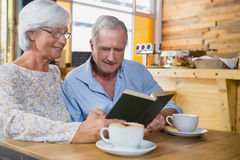 Senior couple reading book while having coffee Royalty Free Stock Images