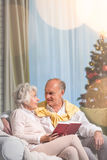 Senior couple reading a book. Senior couple sitting on a sofa at Christmas and reading a book Stock Image
