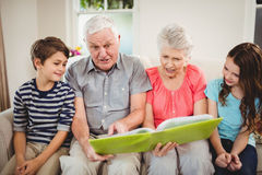 Senior couple reading a book with their grand children Stock Image