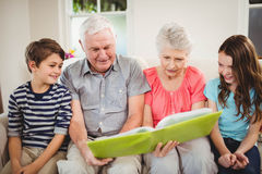Senior couple reading a book with their grand children. Senior couple and their grand children reading a book in living room Royalty Free Stock Photos