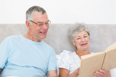 Senior couple reading book together in bed Stock Images