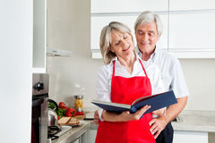 Senior couple reading cookbook. Happy senior couple in kitching looking for recipes in a cookbook Stock Images