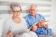 Senior couple reading magazine in bedroom Stock Photo