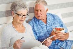 Senior couple reading magazine in bedroom Stock Photos