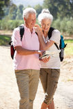 Senior couple reading map on country walk Stock Image