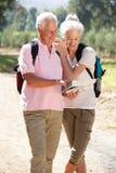 Senior couple reading map on country walk Stock Image