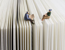 Senior couple reading. Miniature Senior couple reading on a book Royalty Free Stock Photography