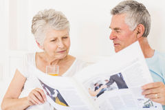 Senior couple reading newspaper. At bed Royalty Free Stock Photos