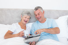 Senior couple reading newspaper in bed Stock Photography