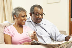 Senior Couple Reading Newspaper At Home Stock Image