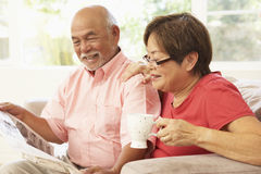 Senior Couple Reading Newspaper At Home. Smiling Stock Photography