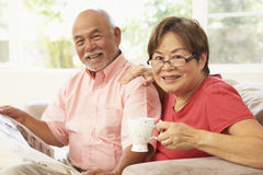 Senior Couple Reading Newspaper At Home Stock Photos
