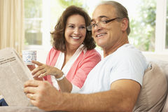 Senior Couple Reading Newspaper At Home. Smiling Royalty Free Stock Images