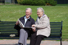 Senior couple reading newspaper on a park bench. A senior couple reading the newspaper on a park bench Royalty Free Stock Photo