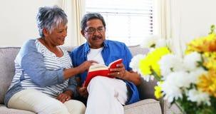 Senior couple reading a novel in living room 4k. Senior couple reading a novel in living room at home 4k stock footage