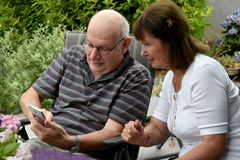 Senior couple reading text messages on mobile phone stock image