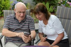 Senior couple reading text messages on mobile phone royalty free stock image
