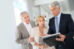 Senior couple with real-estate agent visiting new property. Senior couple with real-estate agent visiting house for sale Royalty Free Stock Photo