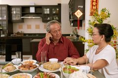 Senior couple receiving disturbing phone call. Worried senior couple sitting at Tet dinner table and calling their relatives, couplets with best wishes for stock photography