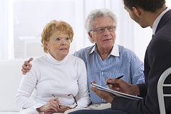 Senior couple receiving  financial planner. Senior couple discussing financial plan with consultant Royalty Free Stock Image