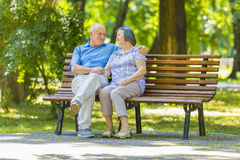 Senior couple relaxed talking on the park bench Royalty Free Stock Images