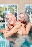 Senior couple relaxes at the edge of the pool. Happy senior couple in the pool together enjoying the wellness vacation royalty free stock photos