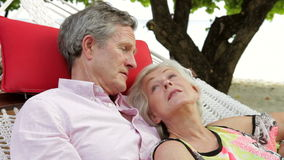 Senior Couple Relaxing In Beach Hammock stock footage
