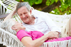 Senior Couple Relaxing In Beach Hammock Stock Images