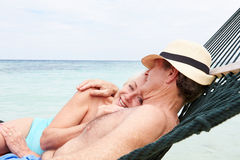 Senior Couple Relaxing In Beach Hammock Royalty Free Stock Image