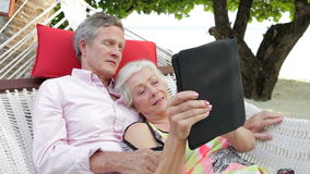 Senior Couple Relaxing In Beach Hammock Using Digital Tablet Stock Photography