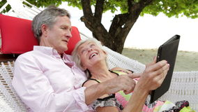 Senior Couple Relaxing In Beach Hammock Using Digital Tablet stock video