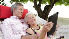 Senior Couple Relaxing In Beach Hammock Using Digital Tablet stock video