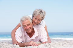 Senior Couple Relaxing On Beach Holiday Stock Photos