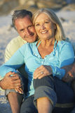 Senior Couple Relaxing On Beach Together In Evening Royalty Free Stock Photo